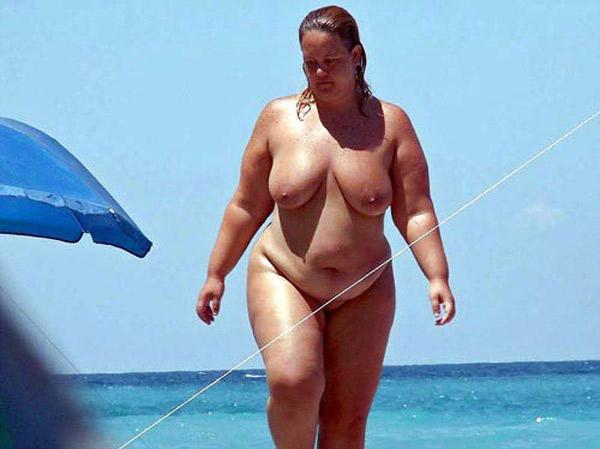 Femme mure naturiste plantureuse nue à la plage